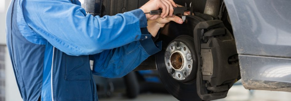 Car mechanic measuring the brake pads on a car